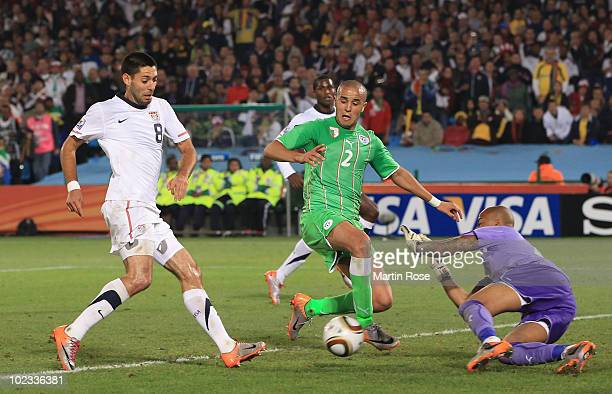 Clint Dempsey of the United States shoots under pressure from Madjid Bougherra of Algeria during the 2010 FIFA World Cup South Africa Group C match...