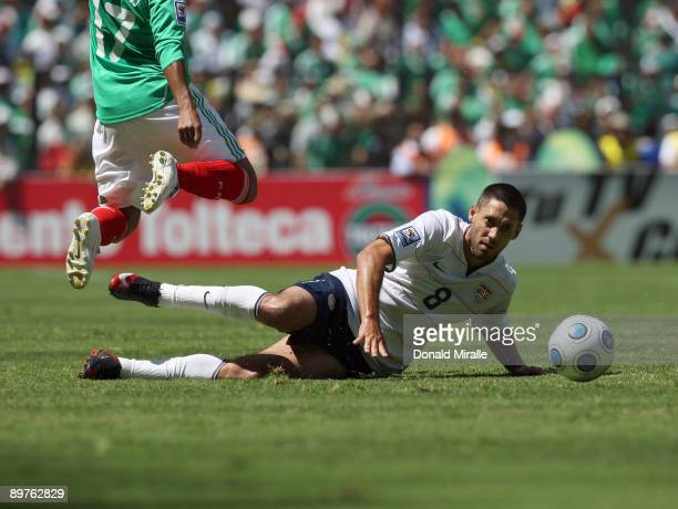 Clint Dempsey of the USA slide tackles for the ball against Giovani Dos Santos of Mexico during the FIFA World Cup Qualifying soccer match between...
