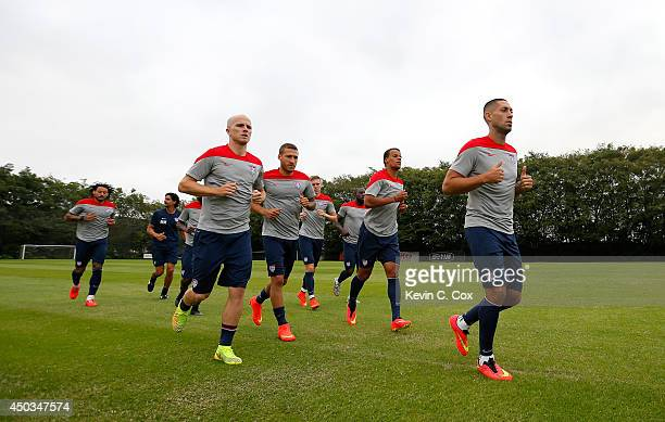 Clint Dempsey Timothy Chandler Fabian Johnson and Michael Bradley of the United States jog around all the fields during the USA training session at...