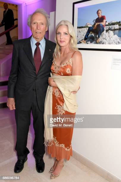 Clint Eastwood and Christina Sandera pose next to his photo at the Vanity Fair and Chopard Party celebrating the Cannes Film Festival at Hotel du...