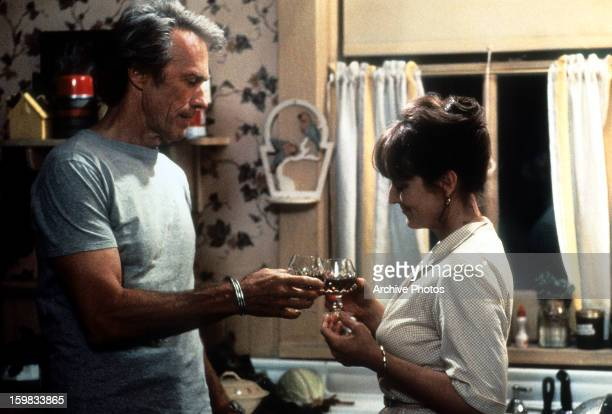 Clint Eastwood and Meryl Streep standing in the kitchen having a cheer in a scene from the film 'The Bridges of Madison County' 1975