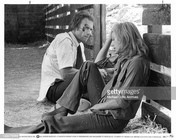 Clint Eastwood and Sondra Locke sitting on the ground of a barn floor talking in a scene from the film 'The Gauntlet' 1977