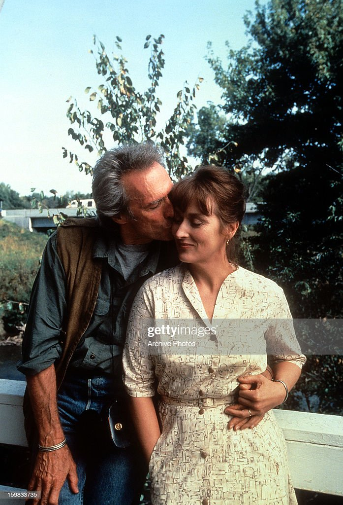 Clint Eastwood kissing Meryl Streep on the cheek as she nestles into him in a scene from the film 'The Bridges of Madison County', 1975.