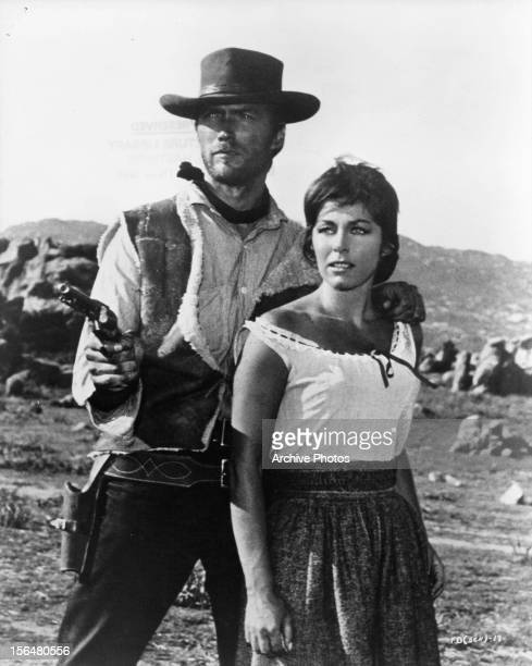 Clint Eastwood points a gun and holds Marianne Koch in a scene from the film 'A Fistful Of Dollars', 1964.