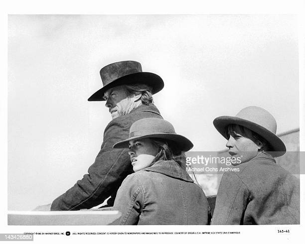 Clint Eastwood standing with Sydney Penny and Carrie Snodgress all looking toward the same direction in a scene from the film 'Pale Rider' 1985