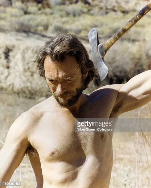 Clint Eastwood US actor bare chested and wielding an axe in an image issued as publicity for the film 'The Outlaw Josey Wales' USA 1976 The Western...