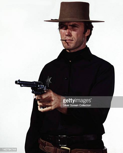 Clint Eastwood US actor in costume smoking a cigar and aiming a pistol in a publicity still issued for the film 'Hang 'Em High' 1968 The Western...