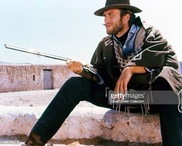 Clint Eastwood US actor smoking a cigar wearing a brown hat and poncho taking aim with a rifle in a publicity portrait issued for the film 'A Fistful...