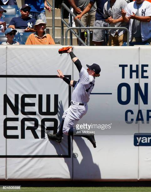 Clint Frazier of the New York Yankees makes a catch at the wall on a ball hit by Adeiny Hechavarria of the Tampa Bay Rays for the final out of the...