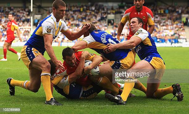 Clint Greenshields of Catalans squeezs through the Warrington defence to score a try during the Carnegie Challenge Cup Semi Final match between...