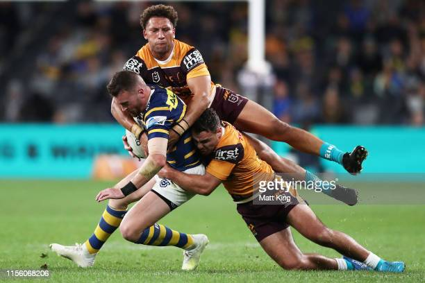 Clint Gutherson of the Eels is tackled by Gehamat Shibasaki and Sean O'Sullivan of the Broncos during the round 14 NRL match between the Parramatta...