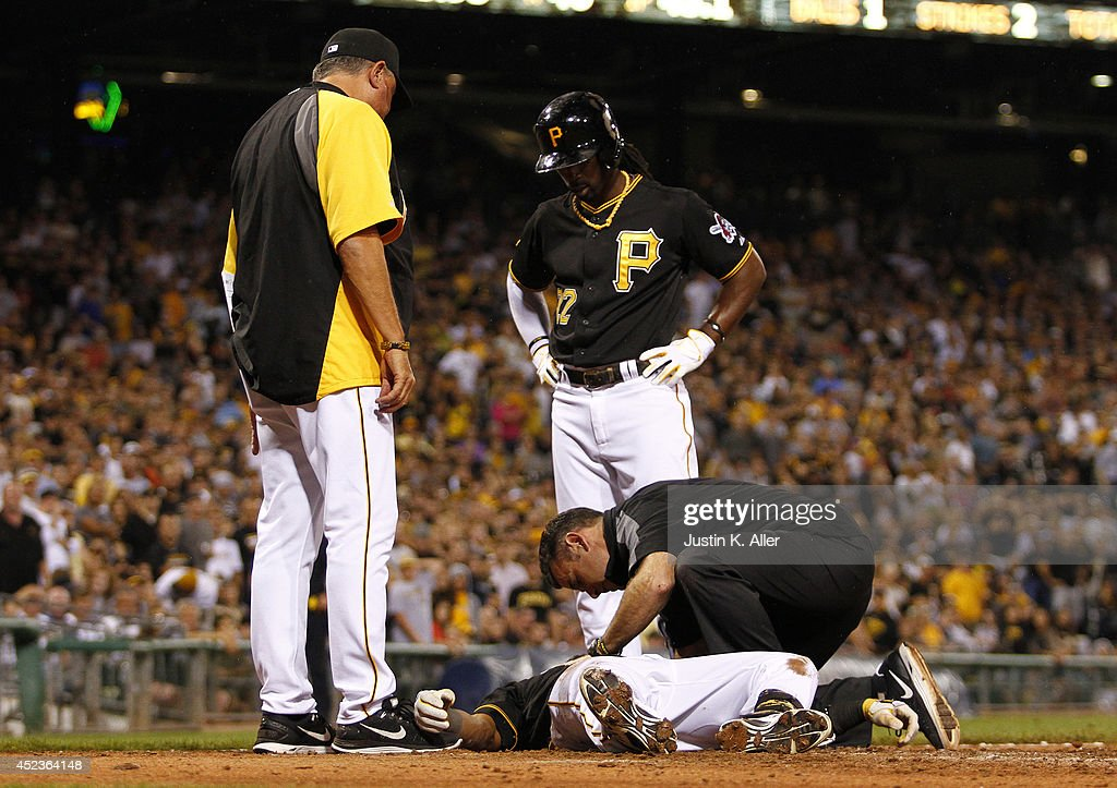Clint Hurdle #13 and Andrew McCutchen #22 of the Pittsburgh Pirates look on as athletic trainer Ben Potenziano tends to Starling Marte #6 after being hit in the head with a pitch in the seventh inning against the Colorado Rockies during the game at PNC Park July 18, 2014 in Pittsburgh, Pennsylvania.