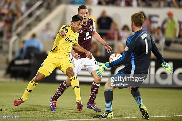 Clint Irwin of the Colorado Rapids makes a save against Jairo Arrieta of the Columbus Crew as Shane O'Neill of the Colorado Rapids tries to stop him...