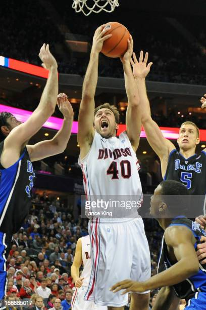 Clint Mann of the Davidson Wildcats goes to the hoop against Ryan Kelly and Mason Plumlee of the Duke Blue Devils at Time Warner Cable Arena on...
