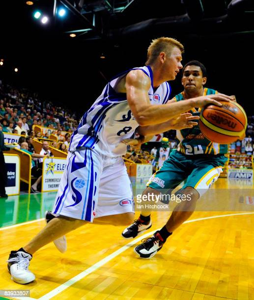 Clint Reed of the Spirit looks to get past Michael Cedar of the Crococdiles during the round 12 NBL match between the Townsville Crocodiles and the...