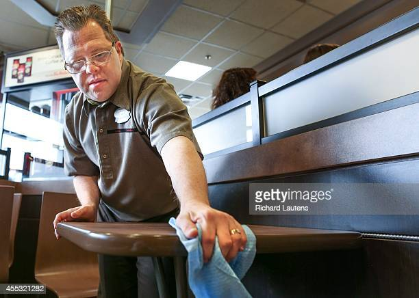 Clint tidies up one of the tables 50 of the 250 employees of Tim Horton franchise owner Mark Wafer have disabilities Clint Sparling is one of those...