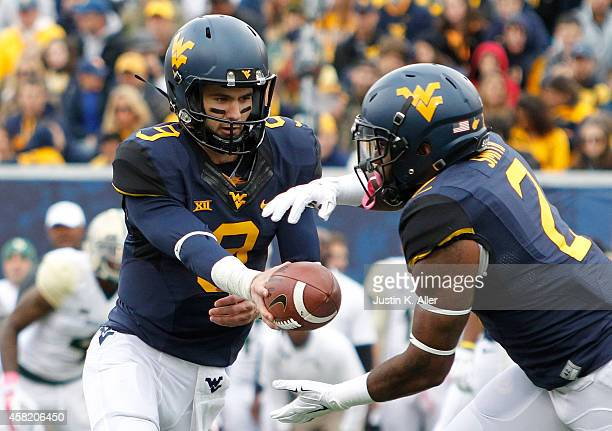 Clint Trickett of the West Virginia Mountaineers hands off during the game against the Baylor Bears on October 18 2014 at Mountaineer Field in...