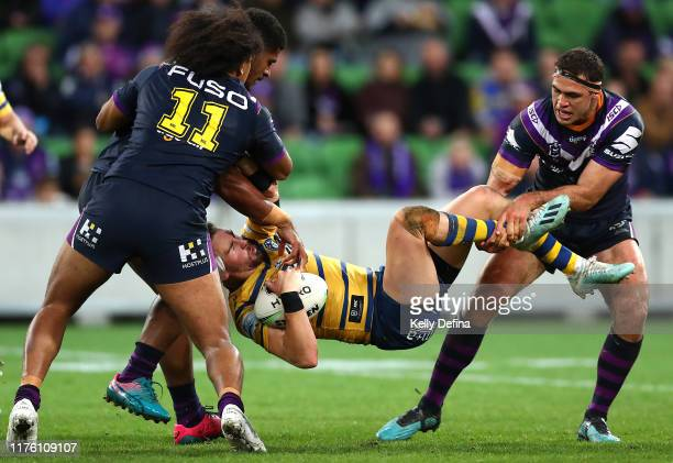 Clinton Gutherson of the Eels is tackled by Dale Finucane of the Storm Tui Kamikamica of the Storm and Felise Kaufusi of the Storm during the NRL...