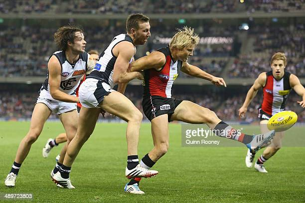 Clinton Jones of the Saints kicks whilst being tackled by Brock McLean of the Blues during the round eight AFL match between the St Kilda Saints and...