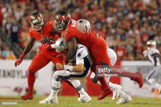 Clinton McDonald of the Bucs jumps on the back of Tom Brady of the Patriots as he sacks the veteran quarterback during the NFL Regular game between...