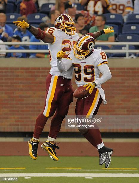 Clinton Portis and Santana Moss of the Washington Redskins jump into the air to celebrate Moss's touchdown against the Detroit Lions at Ford Field on...