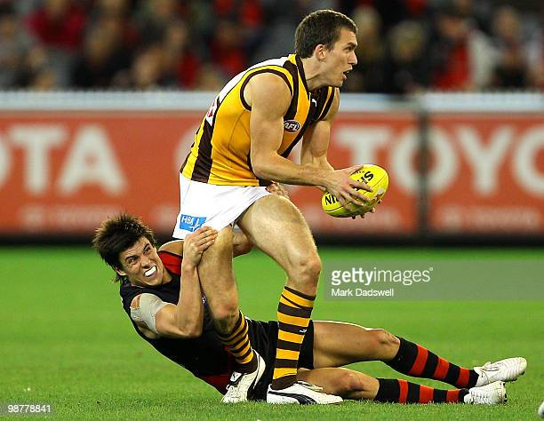 Clinton Young of the Hawks is tackled by Angus Monfries of the Bombers during the round 6 AFL match between the Essendon Bombers and the Hawthorn...