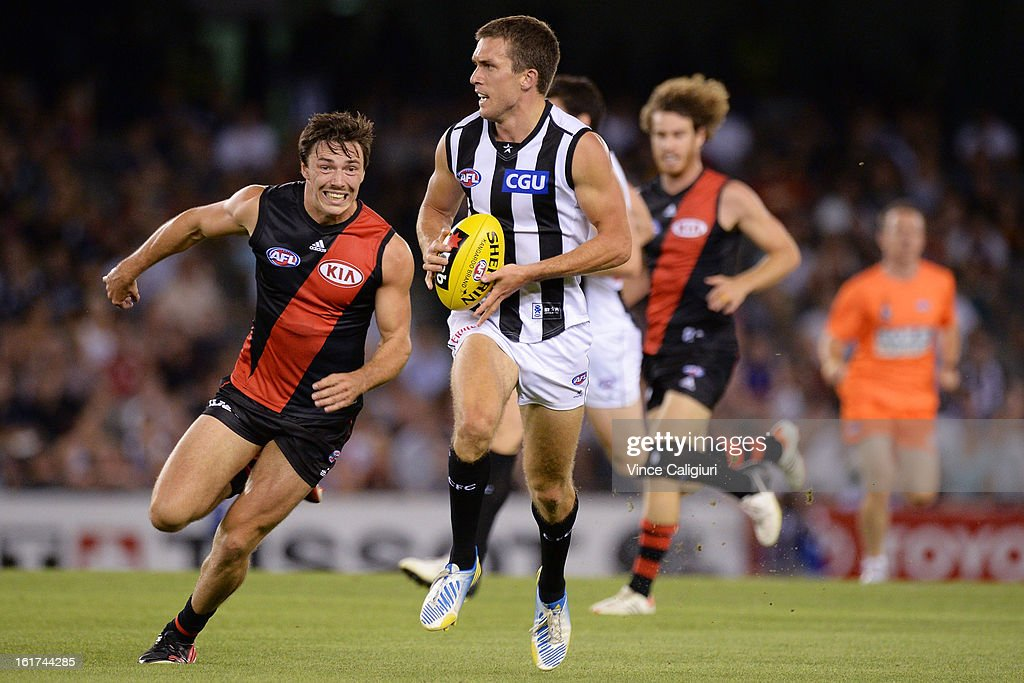 Clinton Young of the magpies runs away from Michael Hibberd of the bombers during the round one AFL NAB Cup match between the Collingwood Magpies and the Essendon Bombers at Etihad Stadium on February 15, 2013 in Melbourne, Australia.