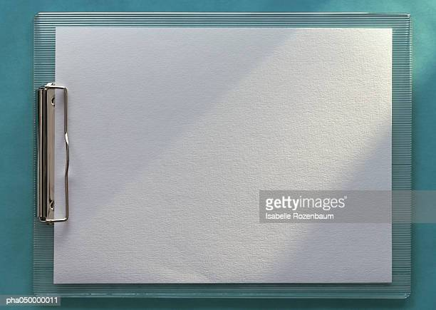 Clipboard holding blank white paper, horizontal, full length, close-up, teal background