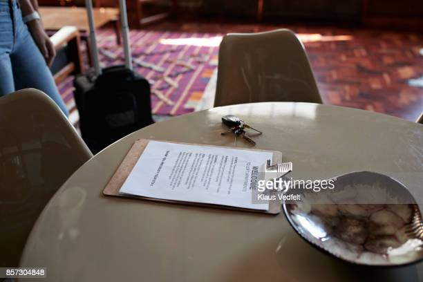 Clipboardwith welcome note, on table in rental apartment
