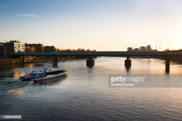 a clipper passenger boat travelling on the river thames by putney bridge - fulham stock pictures, royalty-free photos & images