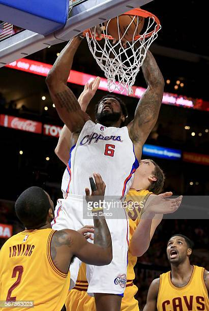 LOS ANGELES CALIF JAN 16 2015 Clippers center DeAndre Jordan powers down a slam dunk against Cavaliers defenders Kyrie irving left Timofey Mosgov and...