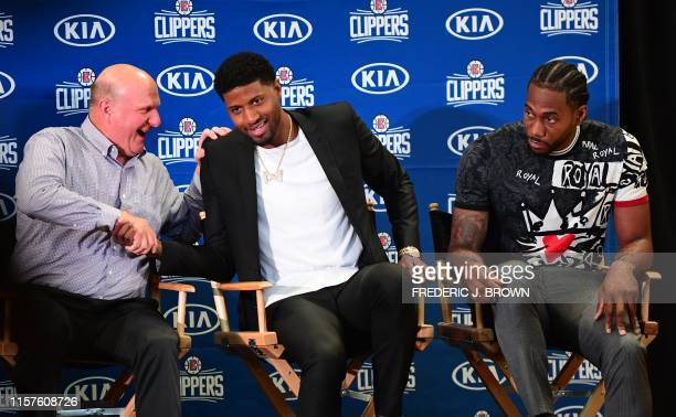 Clippers Owner Steve Ballmer shakes hands with US basketball player Paul George seated beside Kawhi Leonard during a press conference to introduce...