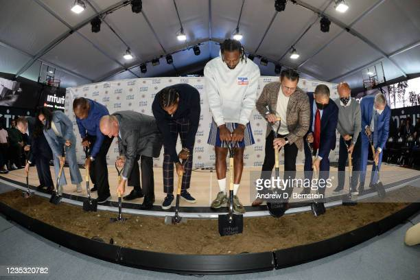 Clippers players, coaches and front office staff, Mayor of Inglewood James T. Butts Jr. And CEO of Intuit Sasan K. Goodarzi dig their shovels into...