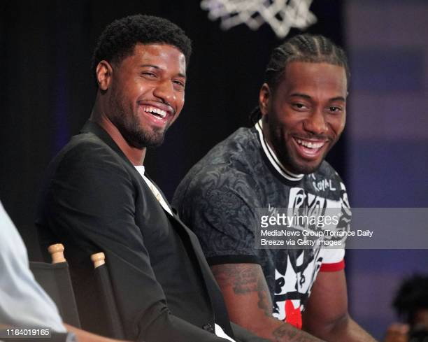 Clippers players Paul George left and Kawhi Leonard laugh at a comment made by owner Steve Ballmer during a press conference at the Green Meadows...