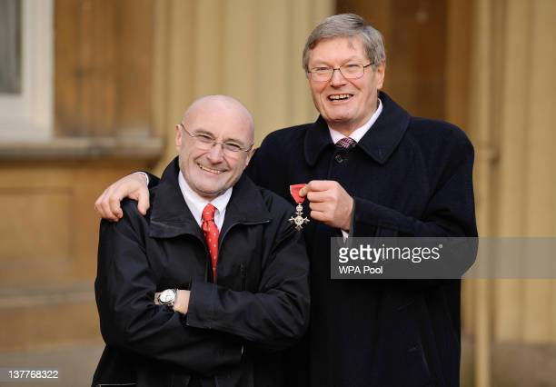 Clive Collins poses with his brother musician Phil Collins after receiving an MBE from Prince Charles Prince of Wales for services to art during an...