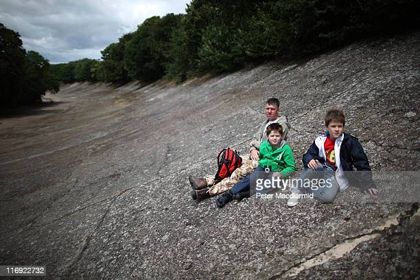 Clive Holloway sits with his son Alexander Holloway and his friend Max Mason on the banked race track as they watch driving tests at The Brooklands...