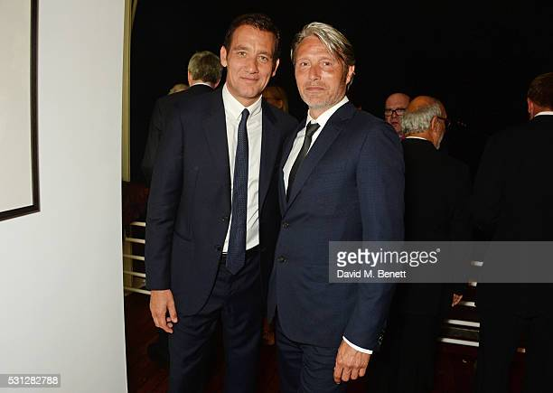 Clive Owen and Mads Mikkelsen attend The 8th Annual Filmmakers Dinner hosted by Charles Finch and JaegerLeCoultre at Hotel du CapEden Roc on May 13...