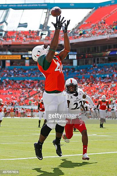 Clive Walford of the Miami Hurricanes catches the ball for a touchdown in front of Zach Edwards of the Cincinnati Bearcats during first quarter...