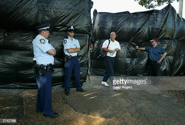 Clive Woodward, the England Head Coach looks at policemen providing security prior to an England training session at Brookvale Oval on November 19,...