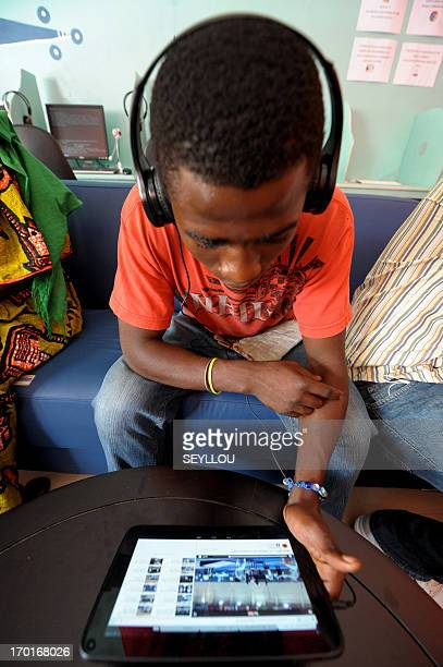 A cllient uses a tablet computer in the world's first cybercafe equipped with tablet computers in the Medina popular district of Dakar on May 28 2013...