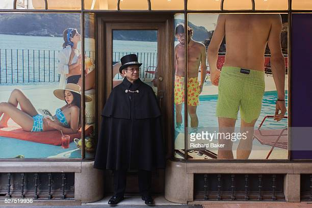 A cloaked guide stands surrounded by a younger generation in beachwear on a poster background in Burlington Arcade in central London Standing still...
