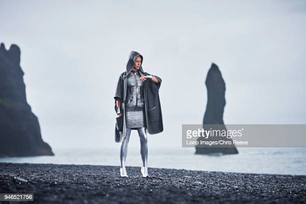 Cloaked young women in silver outfit standing with confidence in front of Basalt rock in southern Iceland