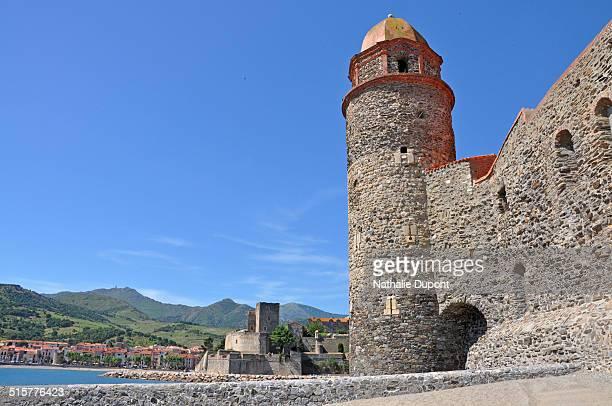 Clocher de l'église Notre-Dame-des-Anges de Collioure avec en arrière-plan le Château Royal et la chaîne des Albères. Photo prise de la plage St...