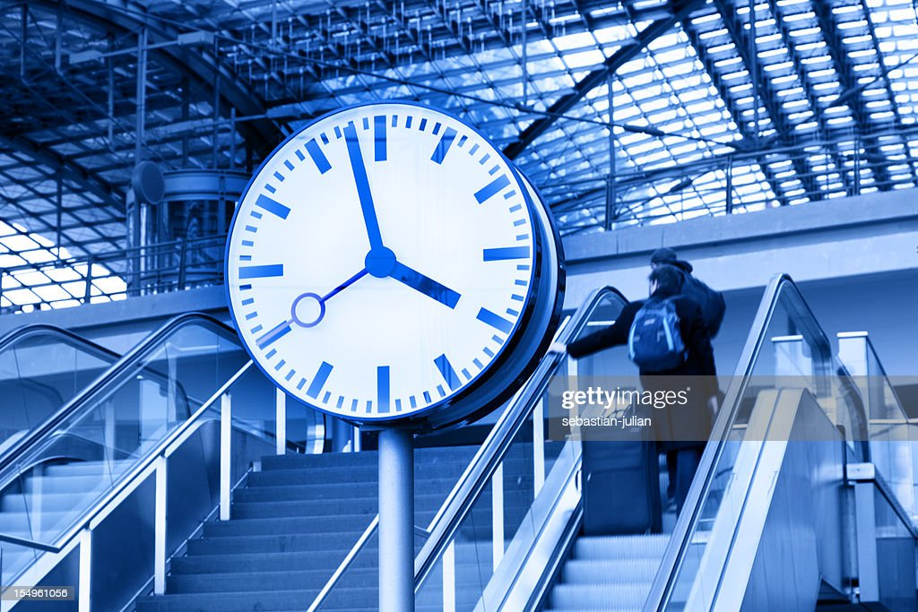 clock and commuters in front of modern railway station ceiling : Stock Photo