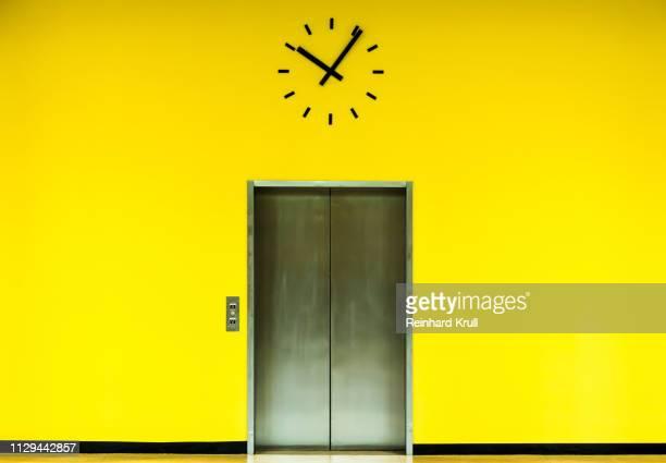 clock and elevator on yellow wall - elevador - fotografias e filmes do acervo
