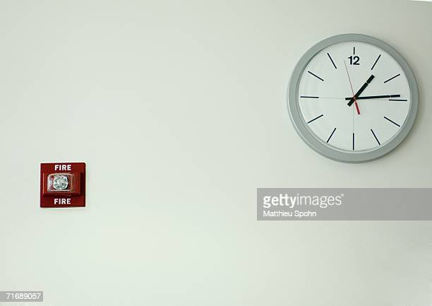 clock and fire alarm on wall - wall clock stock photos and pictures