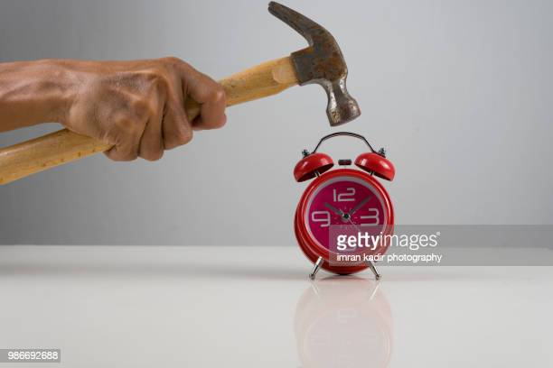 Clock and hammer in grey background