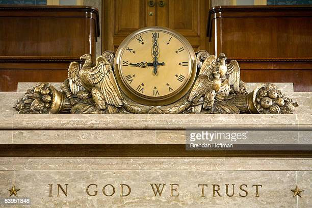 """Clock and the motto """"In God We Trust"""" over the Speaker's rostrum in the U.S. House of Representatives chamber are seen December 8, 2008 in..."""