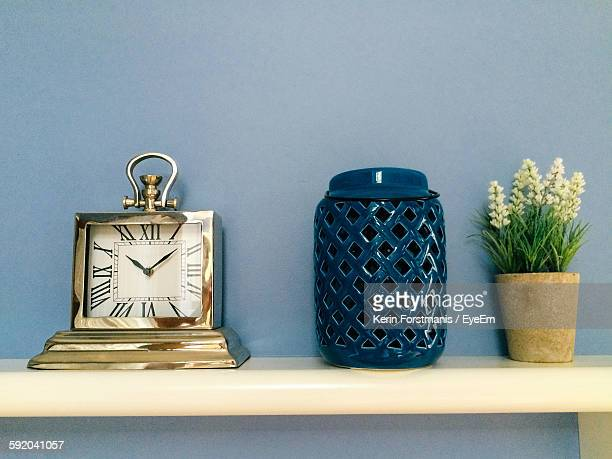 Clock By Lantern And Potted Plant On Shelf Against Wall