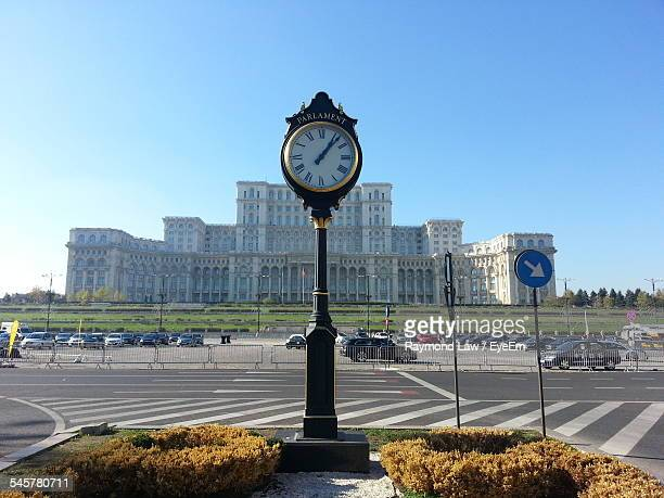 Clock By The Palace Of The Parliament Against Clear Blue Sky